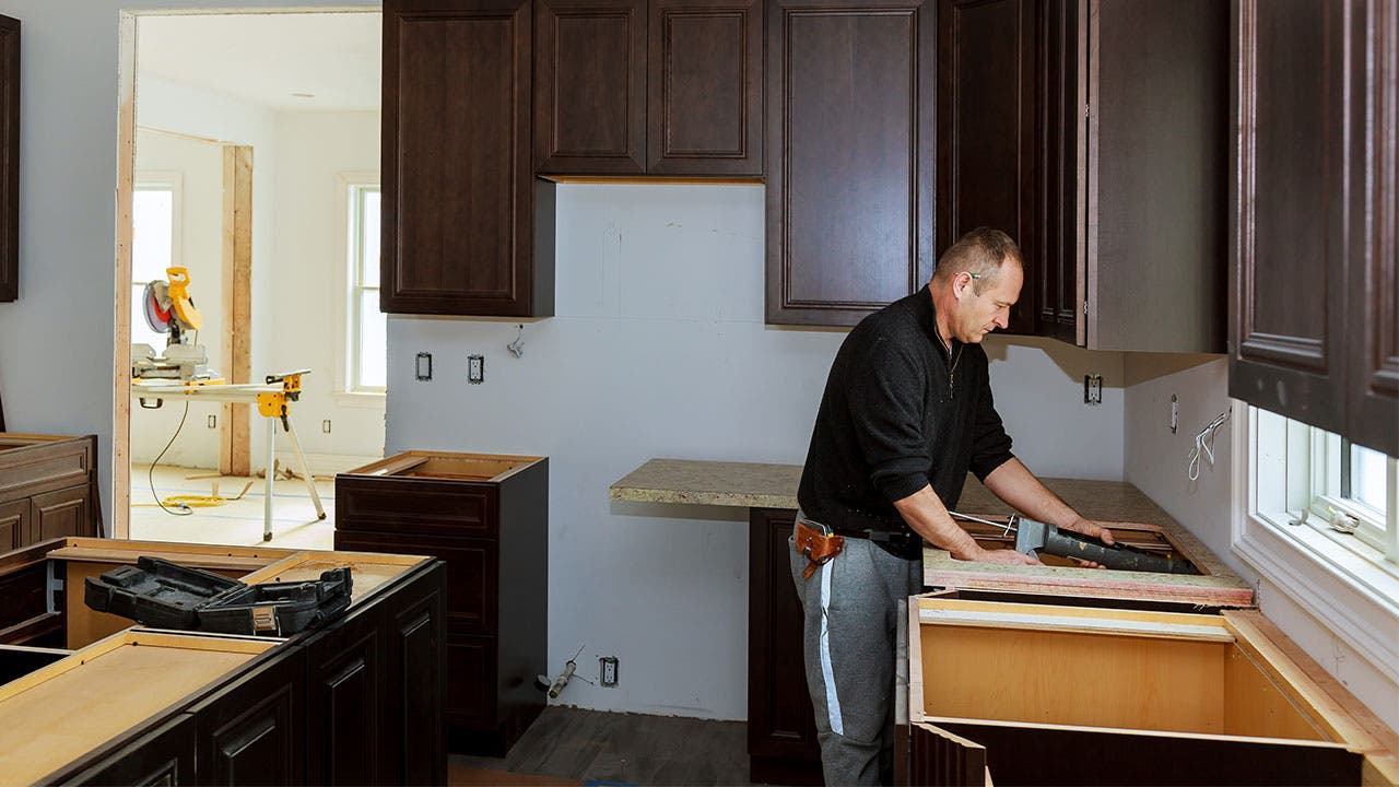 Man installing a counter in kitchen