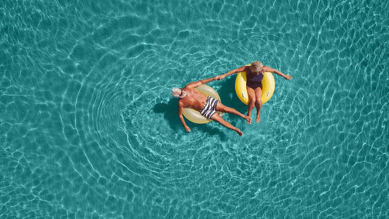 Couple floating on tubes