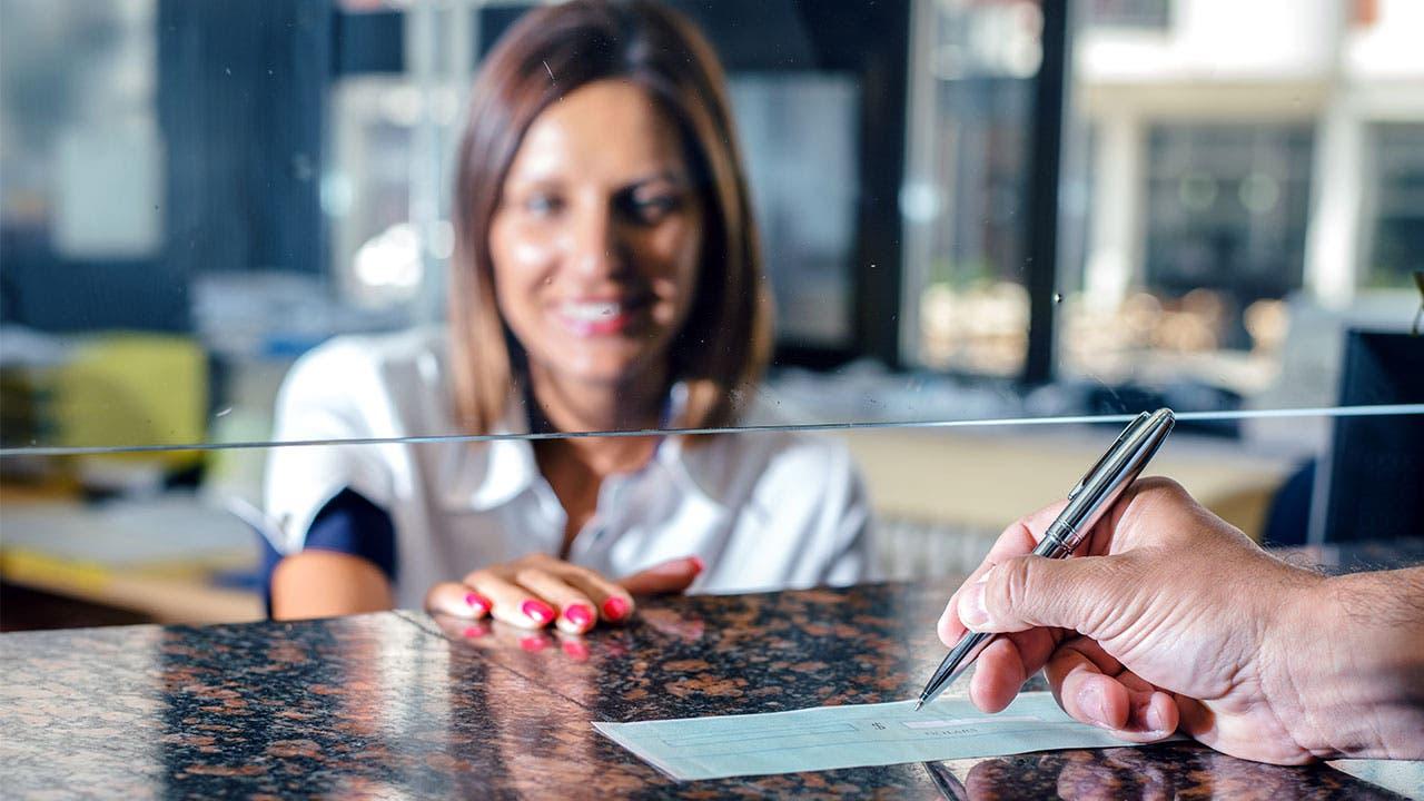 Bank teller and woman signing check
