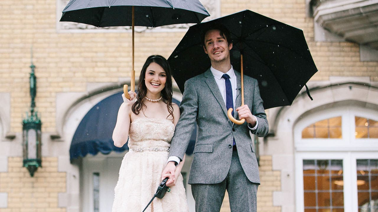 Couple in formal wear with umbrellas