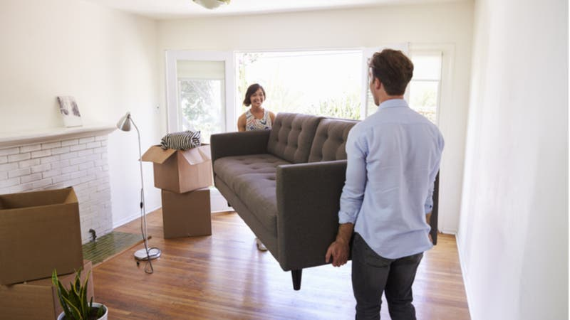 Couple carrying new couch into living room
