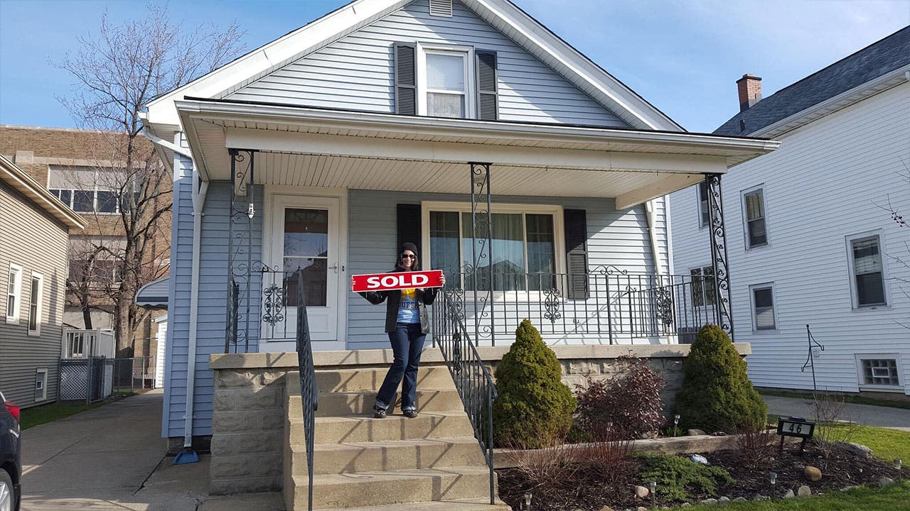 Woman holds up sold sign at new home