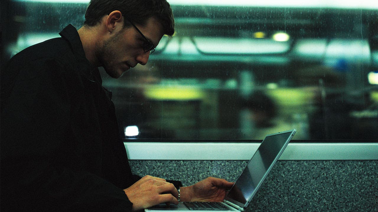 Man using computer on train