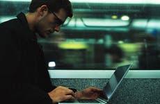 Man using computer on train