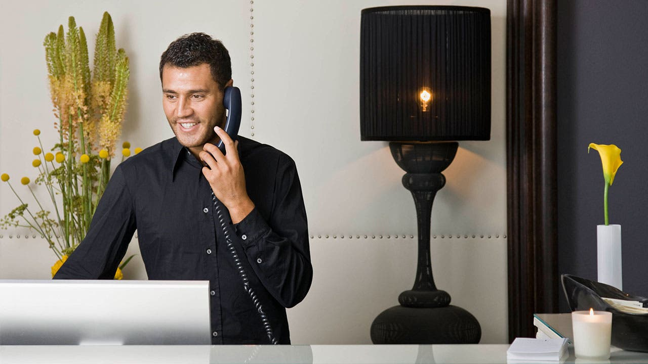 Man at reception desk talking on phone