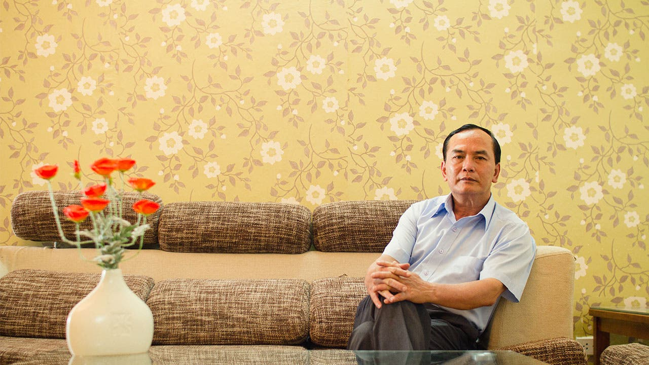Man sitting on couch with dated wallpaper