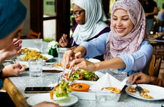 Muslim women in hijabs sharing a meal