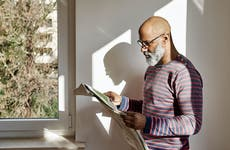 Bearded man reading newspaper