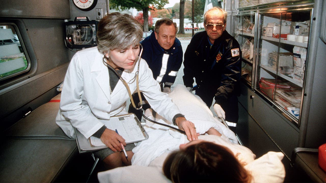 Doctor listening for heartbeat in ambulance