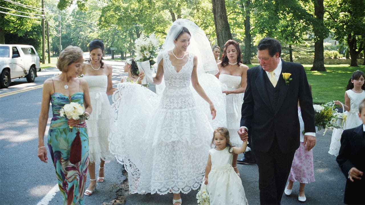 Bride and wedding party walk in street