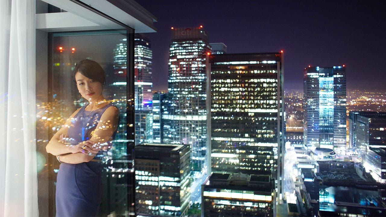 Woman looking outside of a skyscrapper window at night