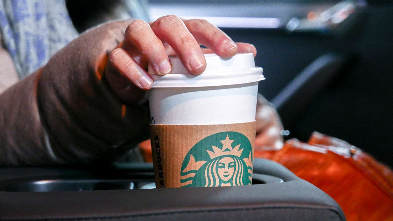 Woman reaching for coffee cup in car