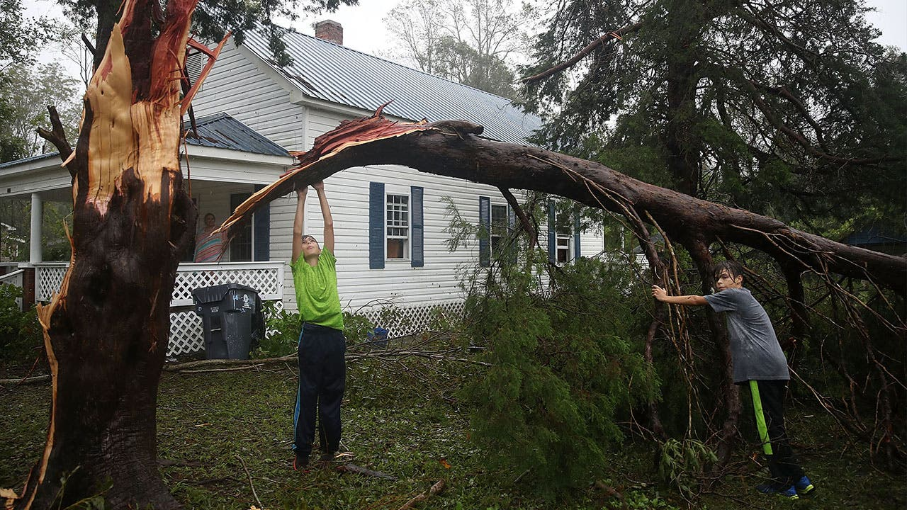 Boys move fallen tree away from house with Hurricane Florence damage all around