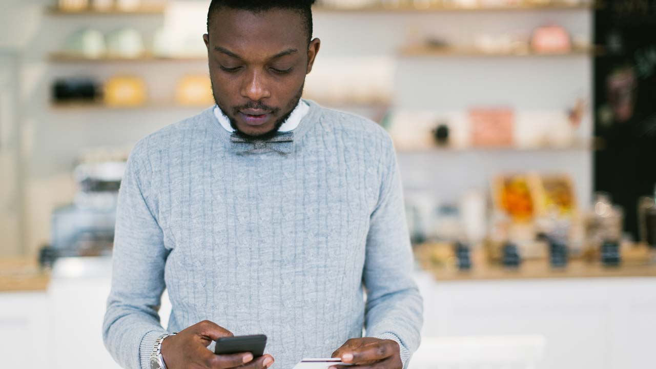 Young man holding debit card and mobile phone