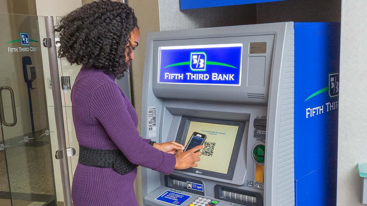 Woman using ATM machine with smartphone