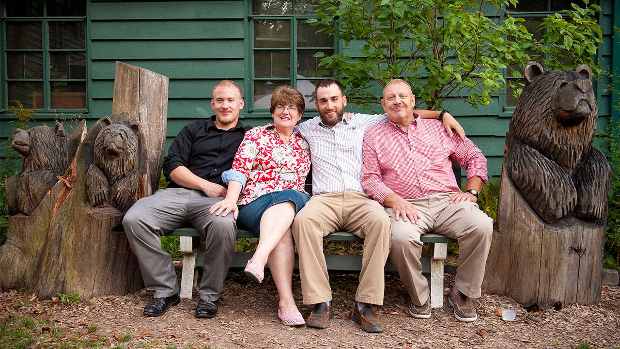 Adult children with their parents sitting on bench