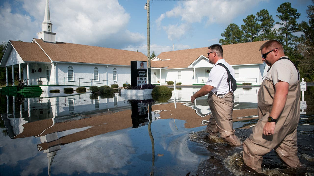 Men walking past church in the aftermath of Hurricane Florence