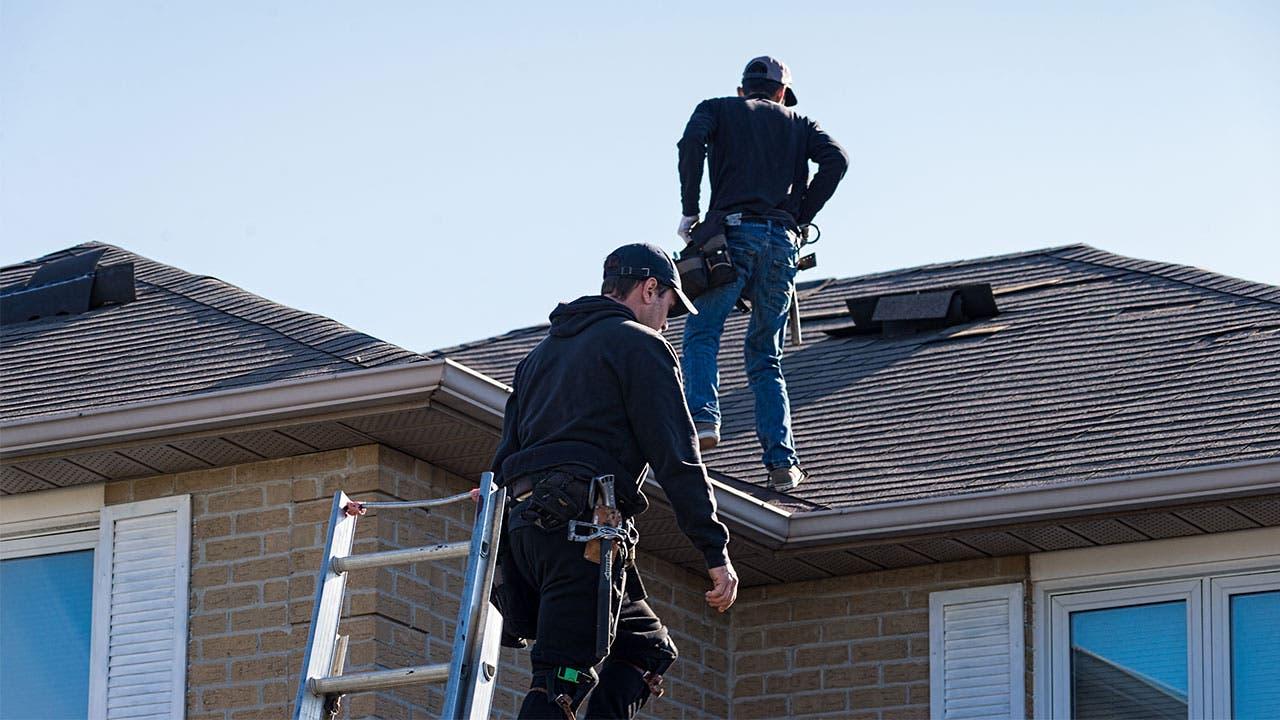 Workers repairing roof