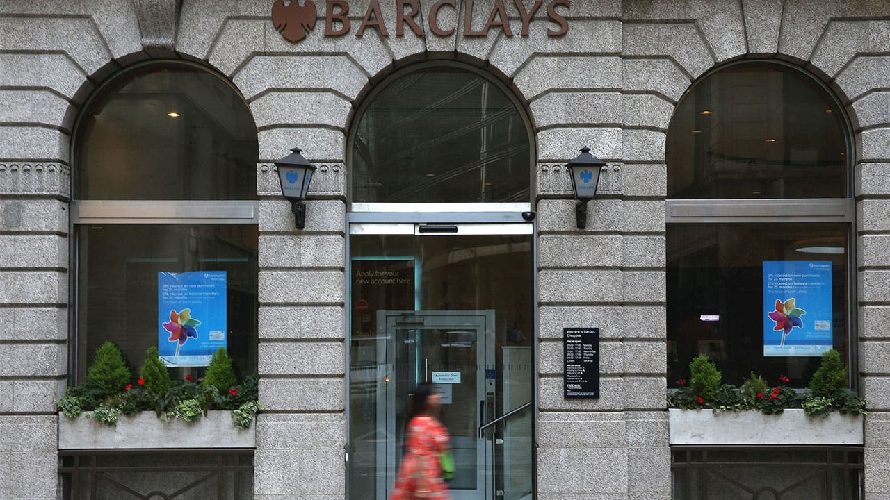 Woman walks past Barclays bank building