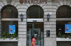 Woman walks past Barclays bank building
