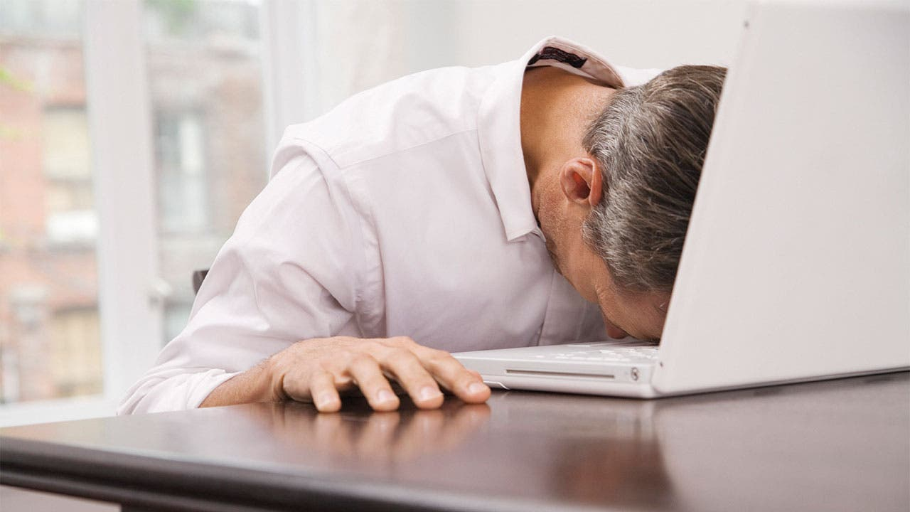 Man stressed at work rests on computer