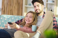 young couple watch TV together on the couch