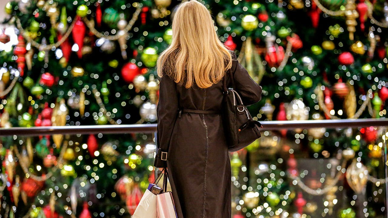 Woman in mall looks at Christmas tree