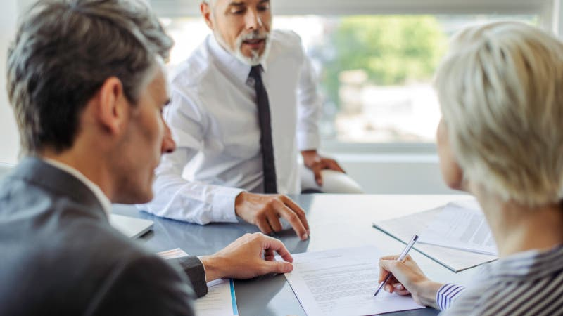 woman signing document in business meeting