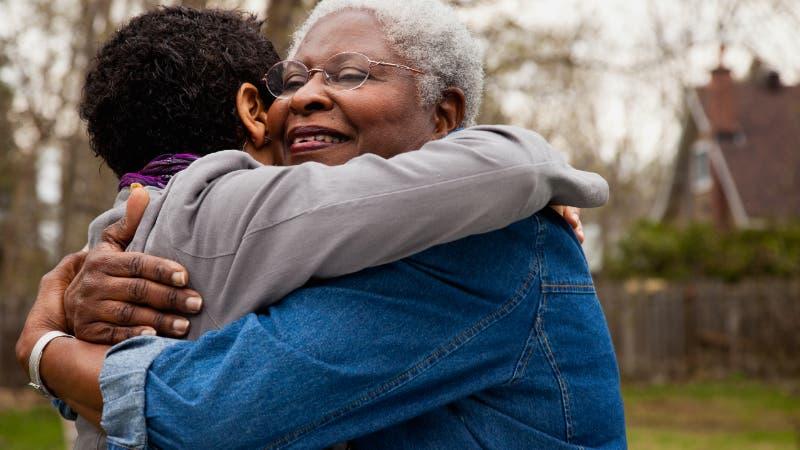 senior African mother hugging daughter