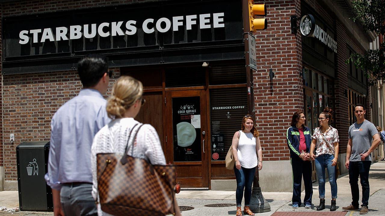 People on corner by Starbucks Coffee store