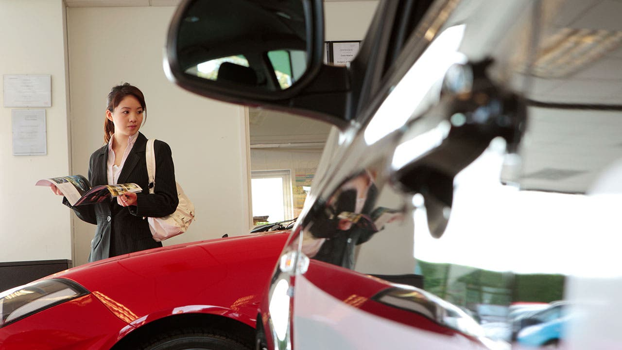 Woman looking at cars in dealership