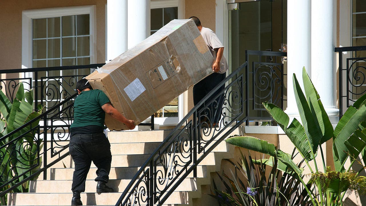 Couple moving furniture into an apartment