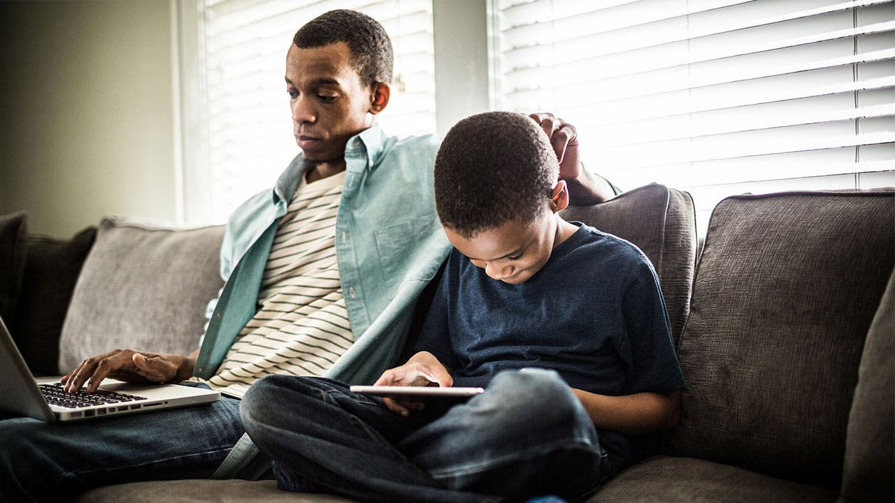 Man and son on computer and tablets