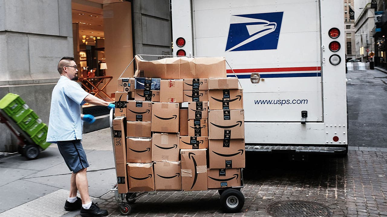 USPS postal worker moving Amazon boxes
