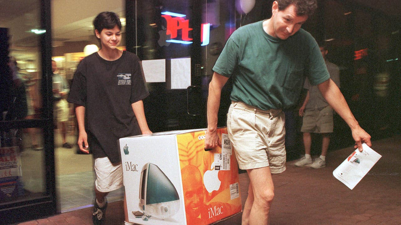 Father and son carrying an iMac