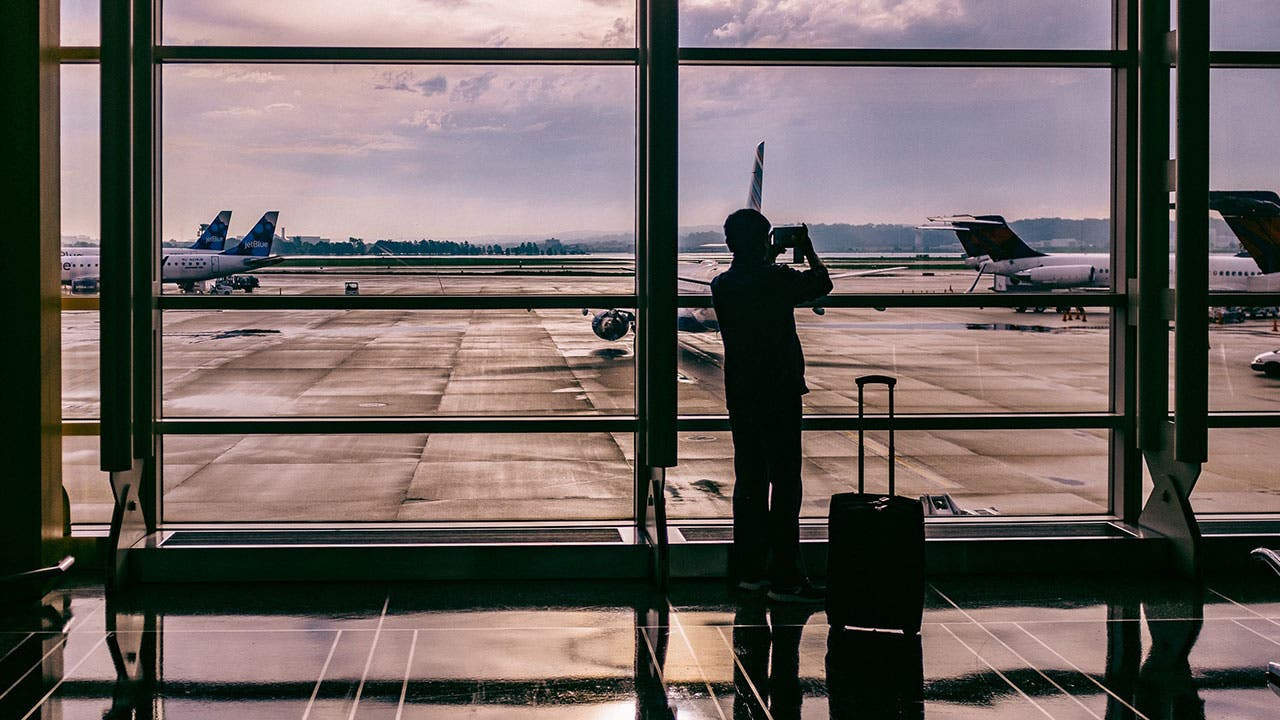 Man taking an picture of plane at airport