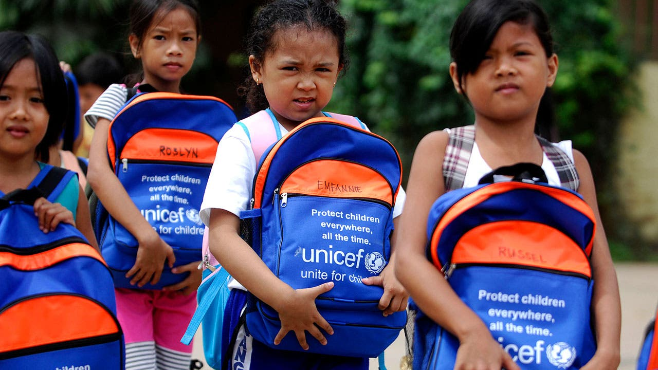 Kids receiving UNICEF backpacks