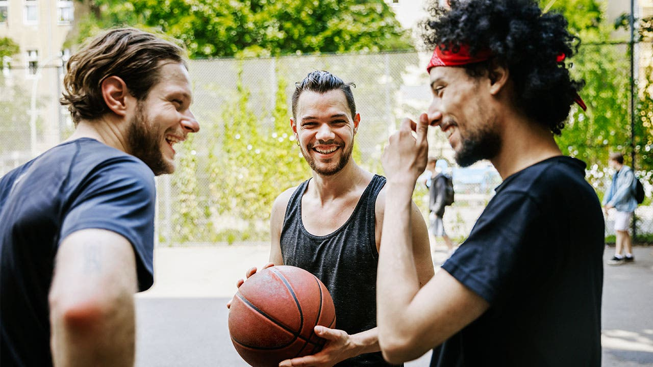 Friends playing basketball in park