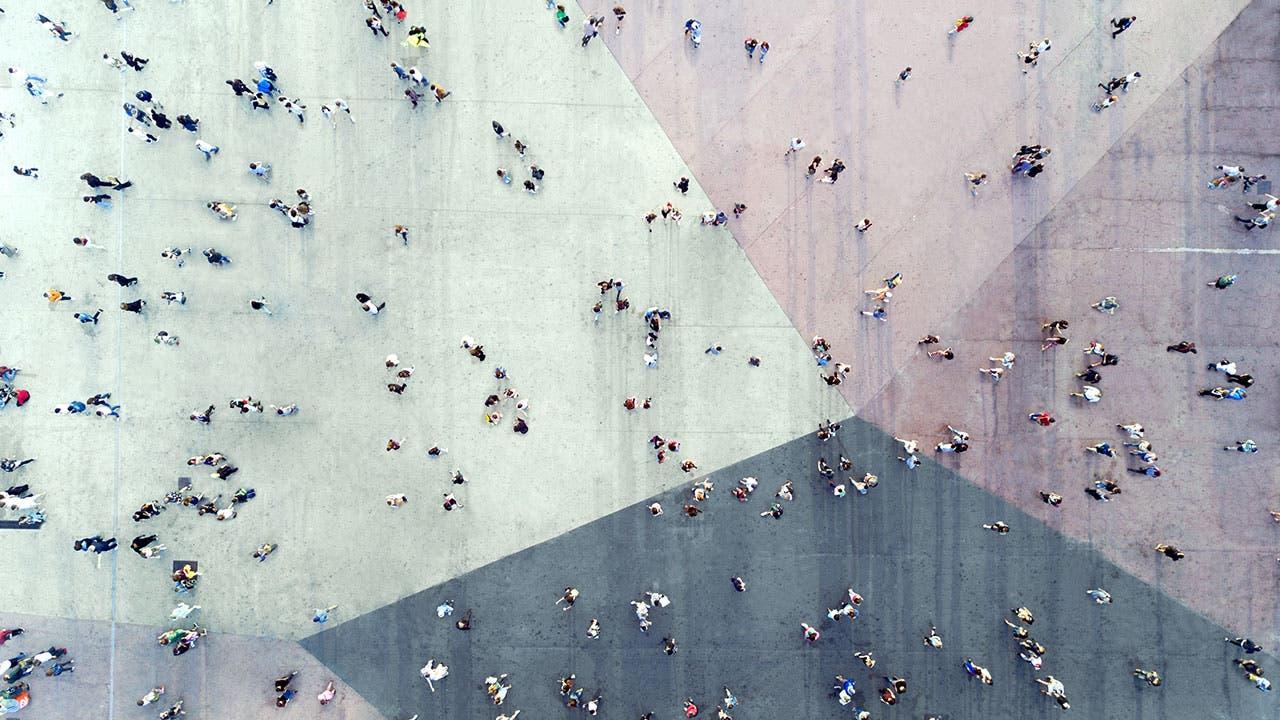 People walking across colored sidewalk