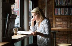 Woman in coffeeshop reviewing paperwork