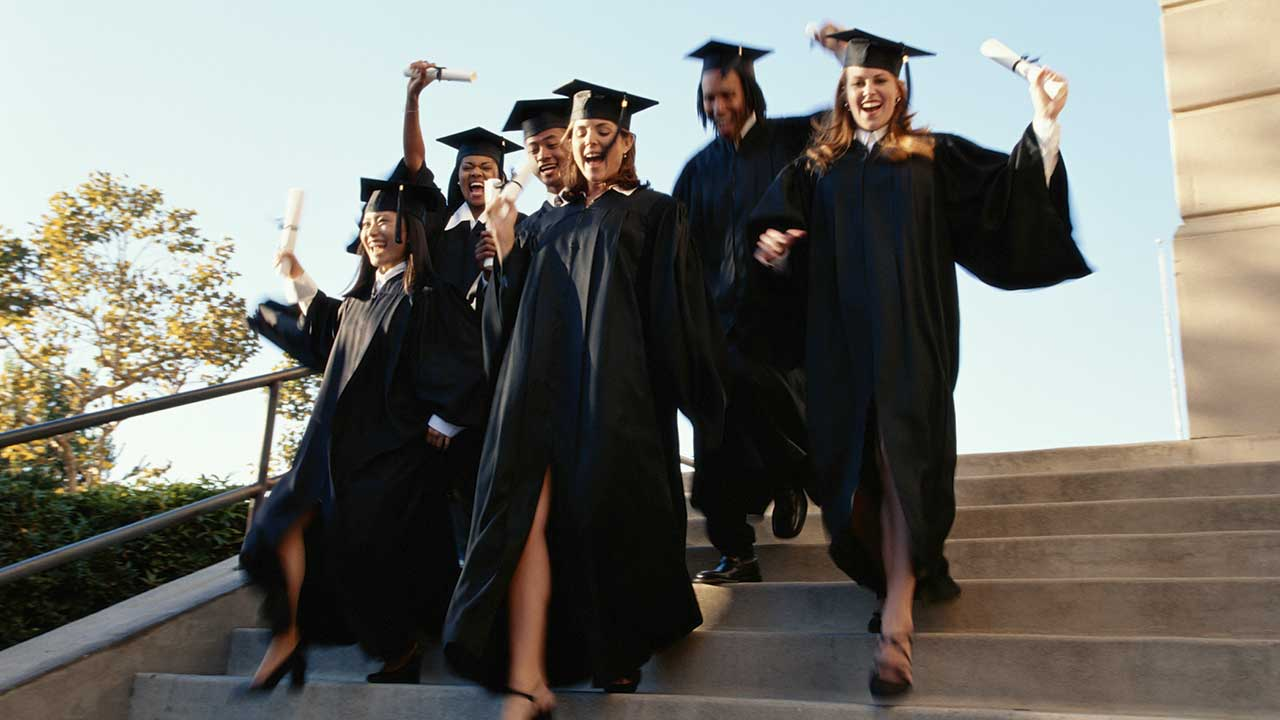 Group of excited graduates running down steps