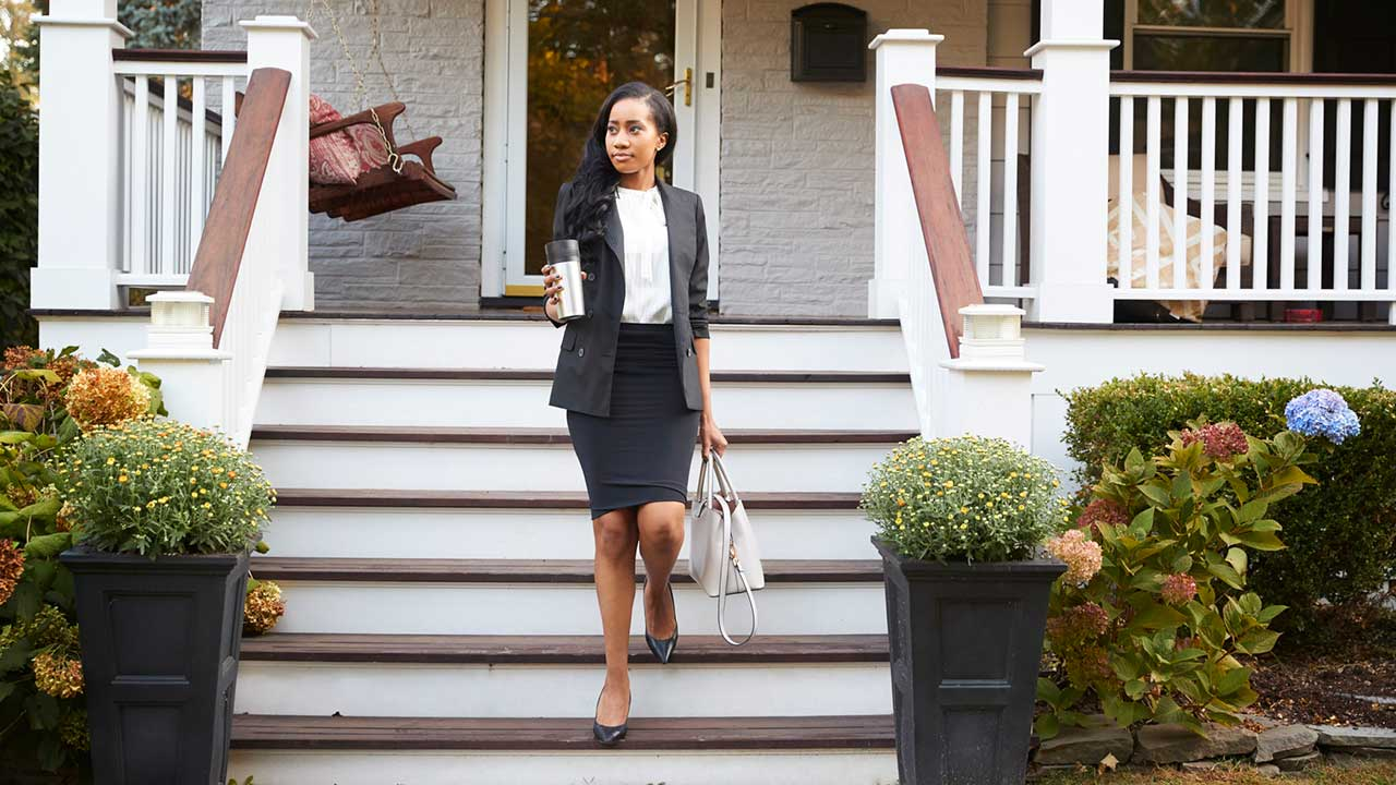 Professionally dressed woman leaving house for work