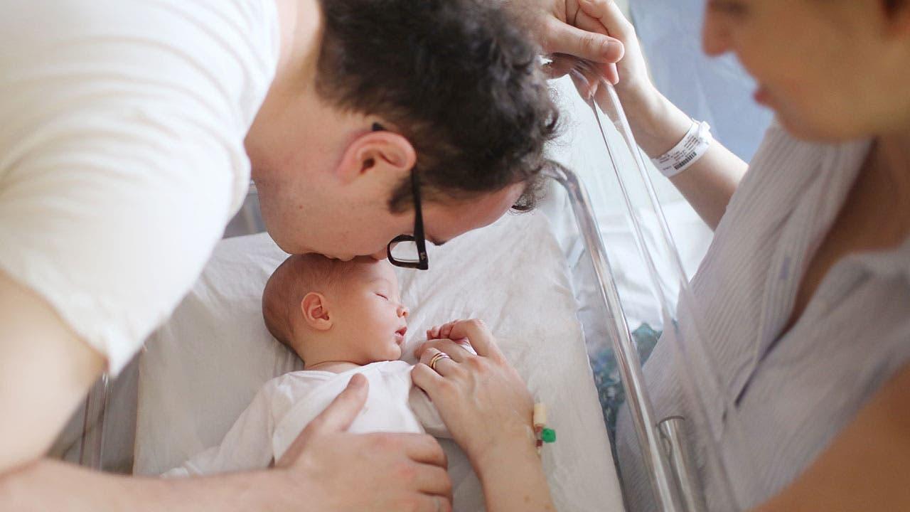 New parents embrace newborn