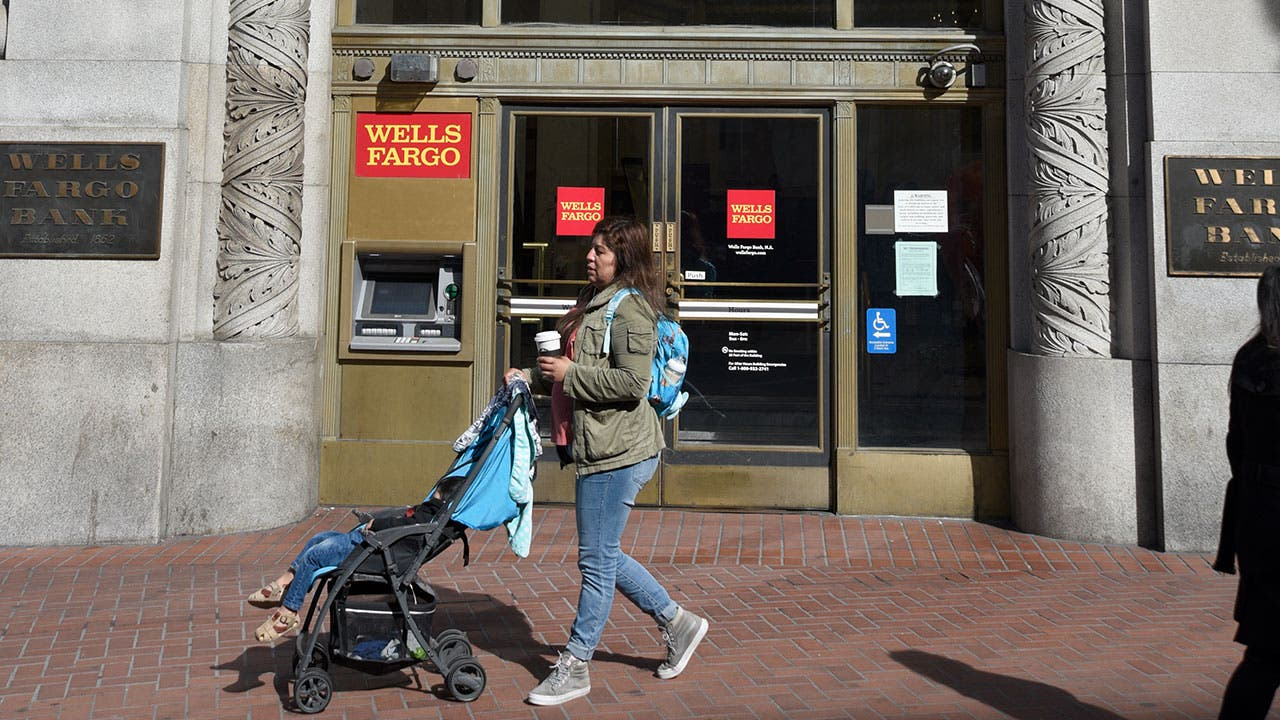 Woman pushing stroller past Wells Fargo bank