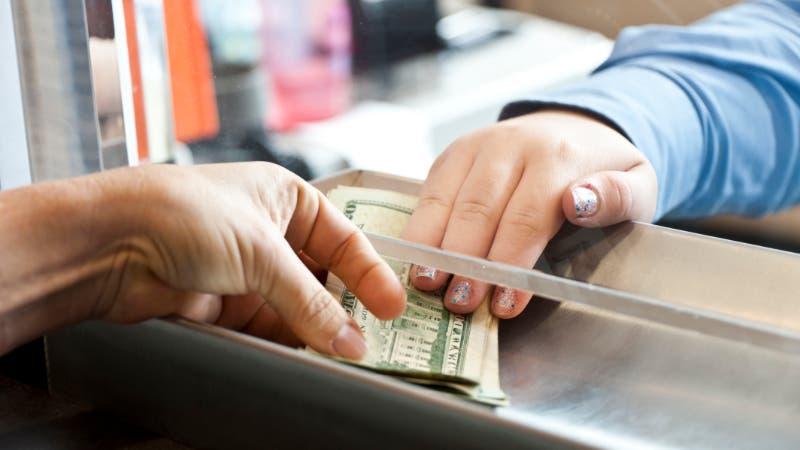 woman handing over cash in bank