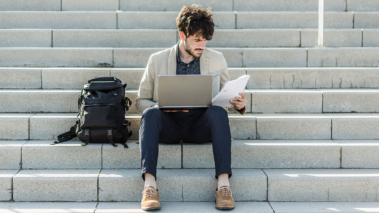 Man using laptop to do banking on steps