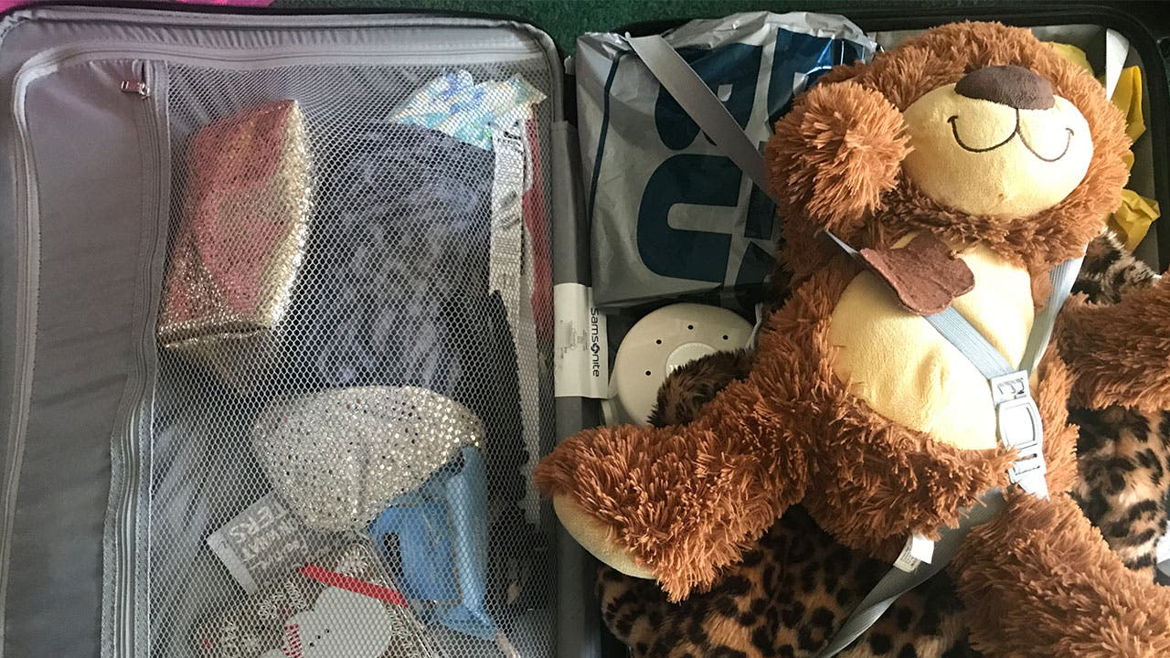 Packed suitcase with teddy bear