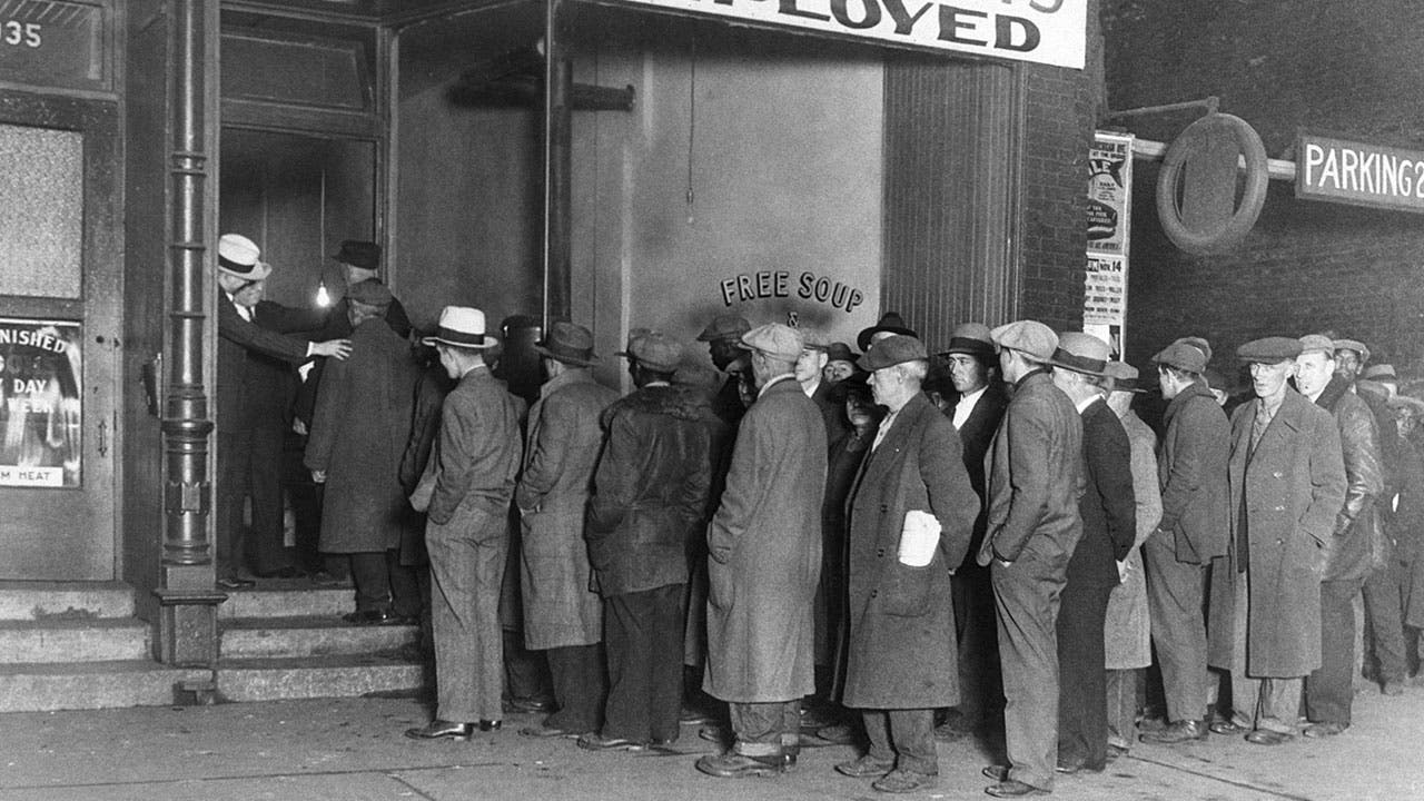 Men stand in line at a soup kitchen during the Great Depression