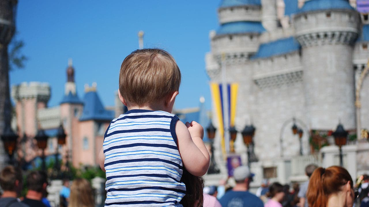 Kid on parents shoulders in Disney World
