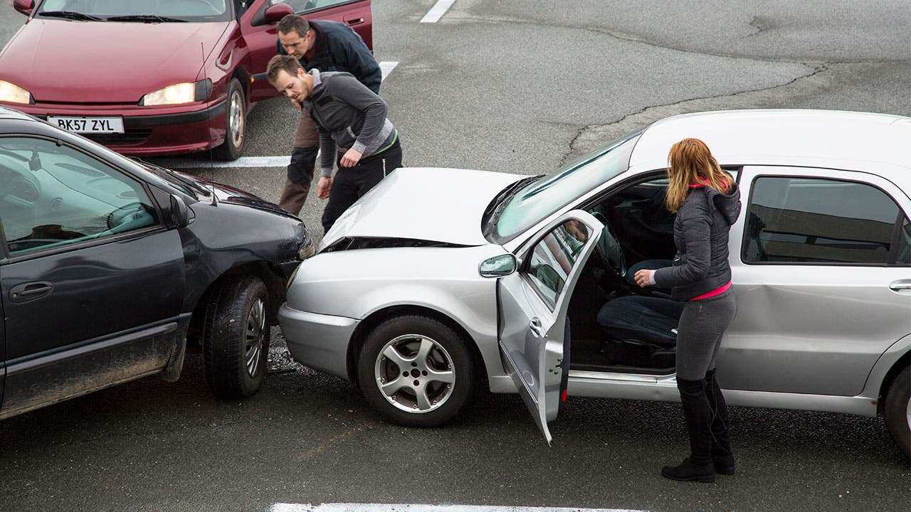 People survey damage after a car collision